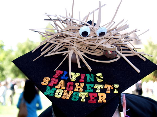 FSM Graduation Cap. This flying spaghetti monster graduation cap is created in a strange shape like a pirate fish with cue eyes. Add some colorful alphabets for its beautiful decor.