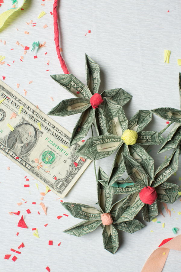 DIY Money Necklace. It's so fantastic to decorate the graduate with this DIY money necklace. Use floral wire to secure the folded bills. Use tissue paper to create the centerpiece. Arrange floral bills on the wire in a beautiful design as you like.
