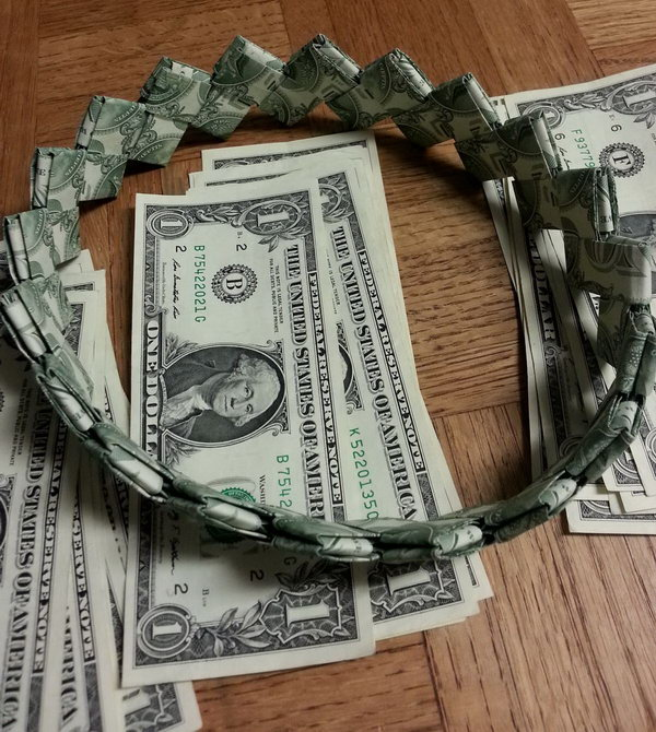 Cash Headband for Graduation. It's boring to send graduate money using envelopes. Try this fun idea to pack your cash as a gift for the graduate. Fold the dollar bill. Take the long end and fold the edge to meet the middle. Assemble and insert one into the other to create the headband.