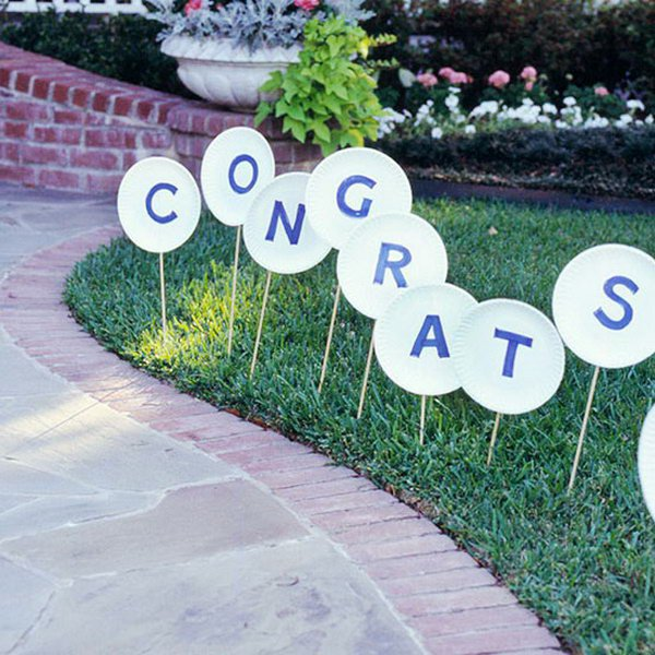 Wooden Sign Graduation Party Decor. Cut out letters and glue to paper plates, attach wooden dowels and stick into the lawn. This graduation decor serves as a direction guide for your party and it can also cut down your party expenditure.