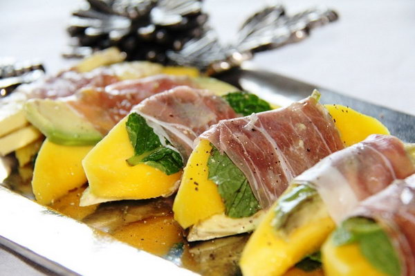 Prosciutto Wrapped Mango Bites. Serve your guests with this quickly served appetizer. Cut mango into slices, lay each slice on srugula and basil. Wrap mango slices in a strip of prosciutto. Add some pepper for ingredients.