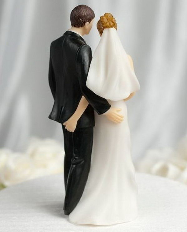 Funny Cake Topper. The bride and groom stand there innocently; however, from behind they are secretly giving each other a 'tender touch'. This funny sexy cake is sure to be a conversation piece at your wedding.