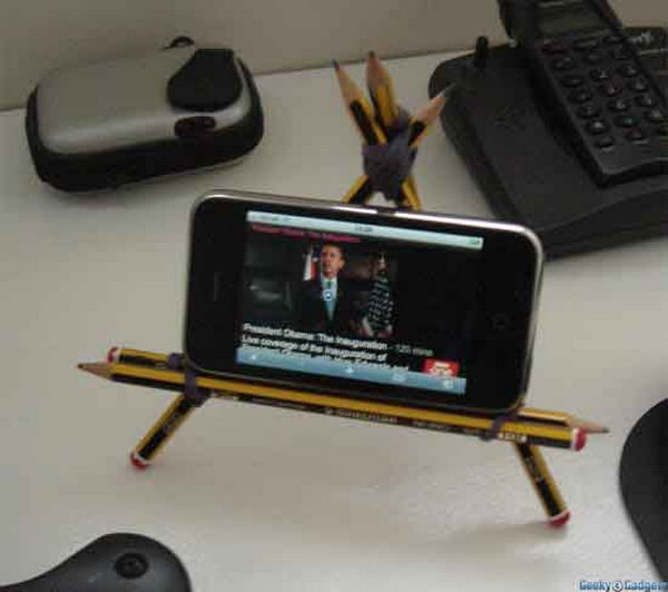 Pencil iPhone Stand. Strap two pencils together with elastic band to make the horizontal support, use more pencils to create a triangle and add one more for back support. It's easy yet very helpful to place your iPhone.