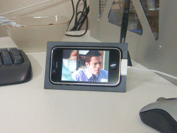 Stand Made from iPhone Packaging. Take advantage of the iPhone packaging by adding 2 jumbo binder clips at the bottom. Glue it at the bottom of the iPhone packaging at the bottom with double sided tape. You can enjoy your movie at a nice angle without holding it for a long time.