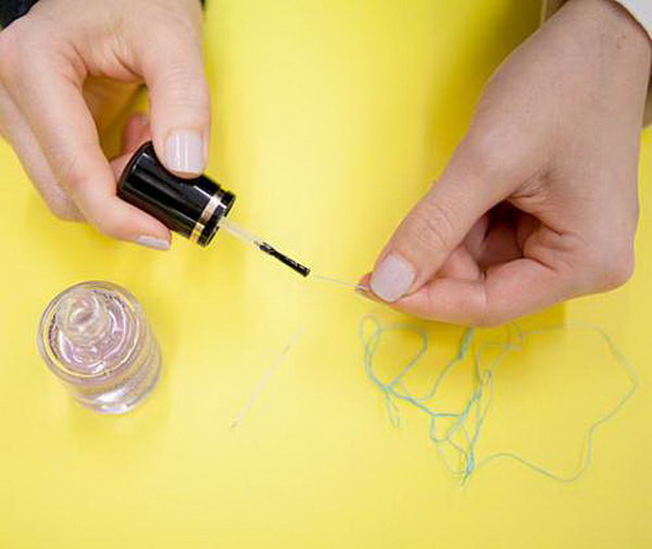 Use clear polish to thread a needle more easily.  Sometimes it's so hard to pull through  a needle. But if you coat the end of the thread with a dot of nail polish, it will be easier to slide through like silk.