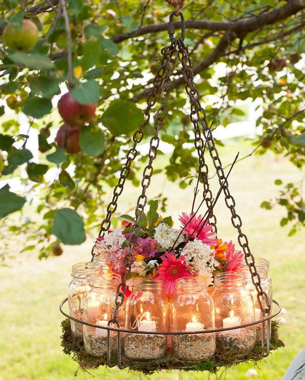 DIY Mason Jar Garden Chandelier. First find a base for the garden chandelier, any shallow tray, pan or basket from an industrial dishwasher is ok. Fill it with fresh arrangements and canning jars with candles in. Now, light candles and enjoy the glow!