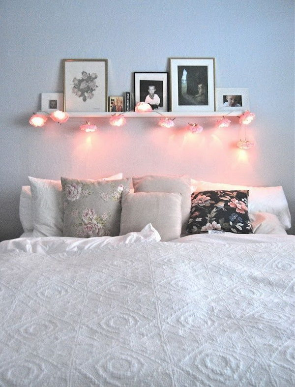 Shelf with Leaning Framed Photos and String Lights.
