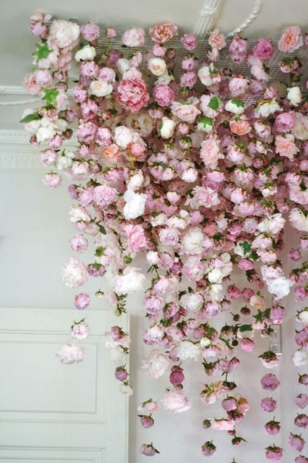 Photo Booth Backdrop With Fake Flowers Hanging From The Ceiling