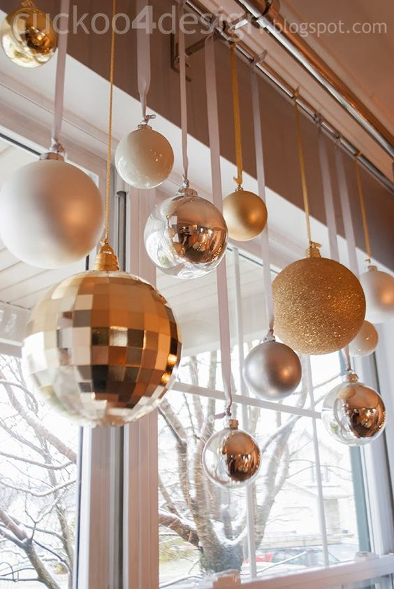 hang christmas ornaments with ribbon off the curtain rod for christmas
