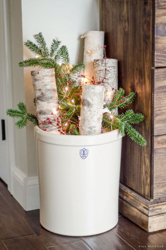 Lit Up Branches and Greenery in an Oversized Crock.