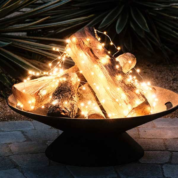 Create A Faux Fire With Fairy Lights Loosely Draped Over A Pile Of Wooden  Logs